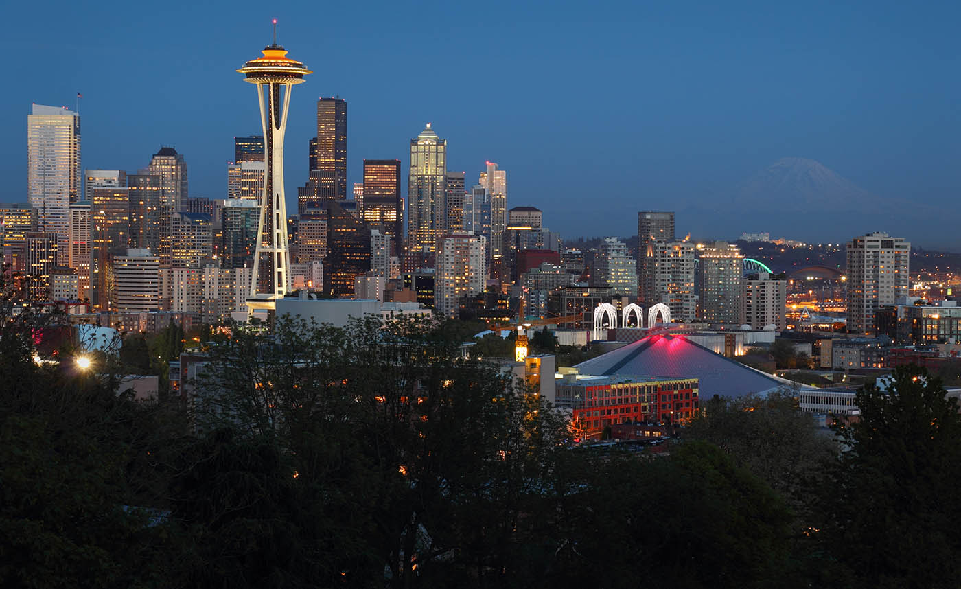 Seattle, Washington skyline at twilight.   lit up as Mt. Rainier fades in the background. USA.