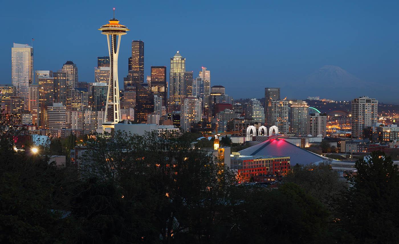 Seattle, Washington skyline at twilight.   lit up as Mt. Rainier fades in the background. USA.