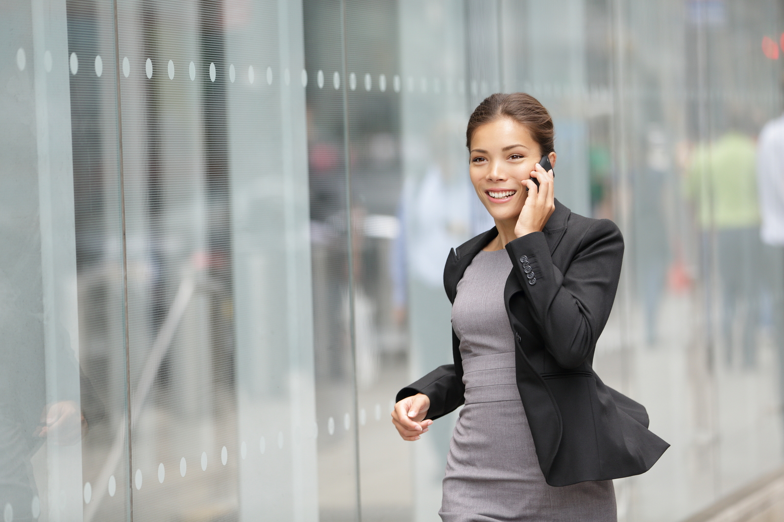 Businesswoman on cellphone running while talking on smart phone. Happy smiling mixed race Asian / Caucasian business woman busy. Image from Manhattan, New York City.